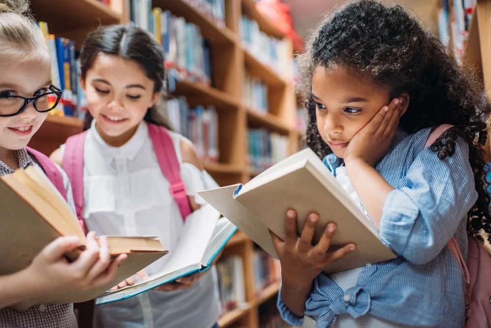 kids-reading-books-in-a-library-in-the-school-holidays